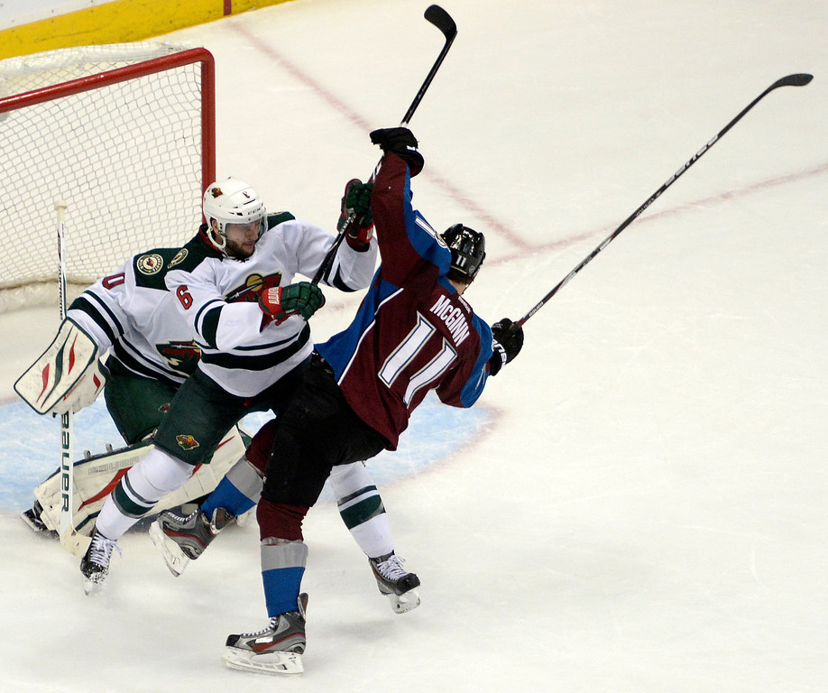 . Marco Scandella (6) of the Minnesota Wild checks Jamie McGinn (11) of the Colorado Avalanche in front of the net being defended by Ilya Bryzgalov (30) of the Minnesota Wild during the first period. The Colorado Avalanche hosted the Minnesota Wild in the first round of the Stanley Cup Playoffs at the Pepsi Center on Saturday, April 19, 2014. (Photo by AAron Ontiveroz/The Denver Post)