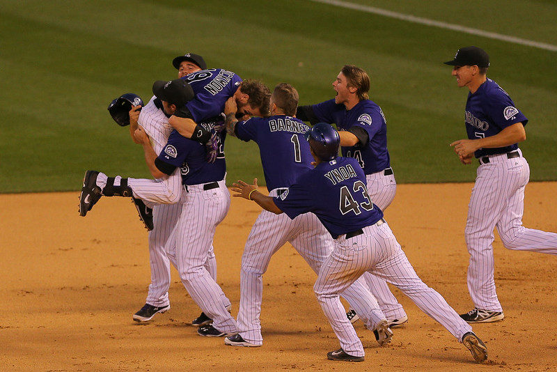 . Charlie Blackmon #19 of the Colorado Rockies is mobbed by teammates after hitting an RBI single for the walk-off 10-9 victory against the San Francisco Giants at Coors Field on September 1, 2014 in Denver, Colorado. (Photo by Justin Edmonds/Getty Images)