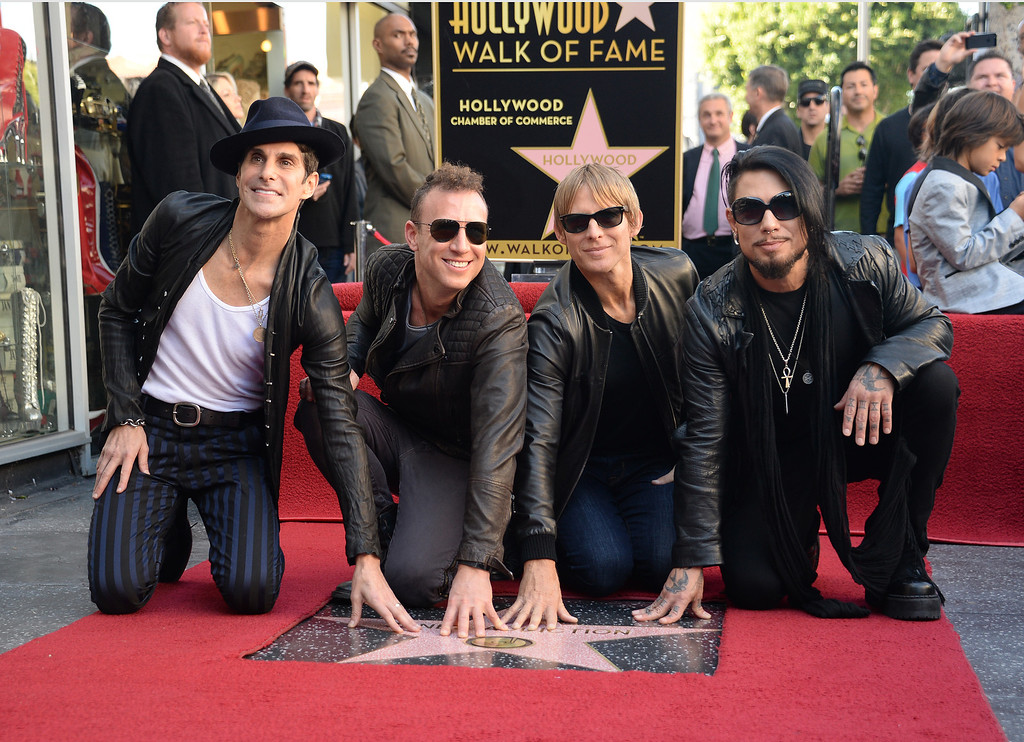 . From left: Perry Farrell, Stephen Perkins, Chris Chaney and Dave Navarro of the alt-rock band Jane\'s Addiction touch their star at the ceremony honoring the band with a star on The Hollywood Walk of Fame, October 30, 2013 in Hollywood, California.           (ROBYN BECK/AFP/Getty Images)