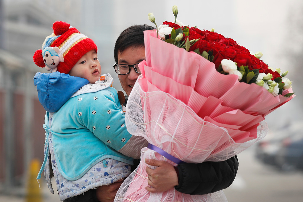 . A man carries his child and a bouquet of Valentine\'s Day roses as he leaves the flower market in Beijing, Tuesday, Feb. 14, 2017. Valentine\'s Day is not a tradition in China but is becoming increasingly popular as Chinese adopt Western customs, encouraged by retailers who see them as a way of boosting sales. (AP Photo/Andy Wong)