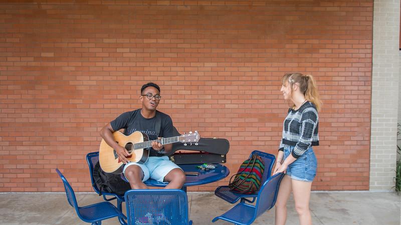 Antony Lametrie (Left) plays his guitar for Olivia Whitehurst in the Center for Instruction Courtyard.