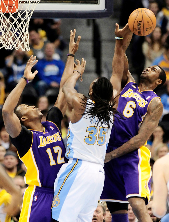 . Los Angeles Lakers\' Dwight Howard (L) and Earl Clark (R) block Denver Nuggets\' Kenneth Faried during their NBA basketball game in Denver, Colorado February 25, 2013.   REUTERS/Mark Leffingwell