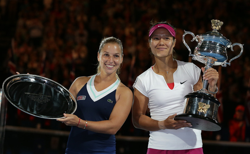 . Li Na of China, right,  holds the championship trophy with second placed Dominika Cibulkova of Slovakia  in their women\'s singles final at the Australian Open tennis championship in Melbourne, Australia, Saturday, Jan. 25, 2014.(AP Photo/Aaron Favila)