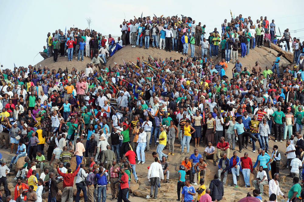 Description of . People gather on a hill in Marikana on August 23, 2012 after attending a memorial service for the 44 people killed in a wildcat strike at Lonmin's Marikana mine. Lonmin and nearby Impala Platinum closed for the day as workers prepared for memorials, including the main national service at Marikana where police gunned down 34 miners a week ago after deadly clashes had already claimed 10 people. The service at Lonmin will be the focal point during a day of mourning that will stretch across the country, as many of the victims were migrant workers whose bodies have already returned to their home villages. AFP PHOTO / STR-/AFP/Getty Images