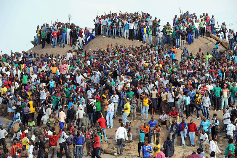 . People gather on a hill in Marikana on August 23, 2012 after attending a memorial service for the 44 people killed in a wildcat strike at Lonmin\'s Marikana mine. Lonmin and nearby Impala Platinum closed for the day as workers prepared for memorials, including the main national service at Marikana where police gunned down 34 miners a week ago after deadly clashes had already claimed 10 people. The service at Lonmin will be the focal point during a day of mourning that will stretch across the country, as many of the victims were migrant workers whose bodies have already returned to their home villages. AFP PHOTO / STR-/AFP/Getty Images