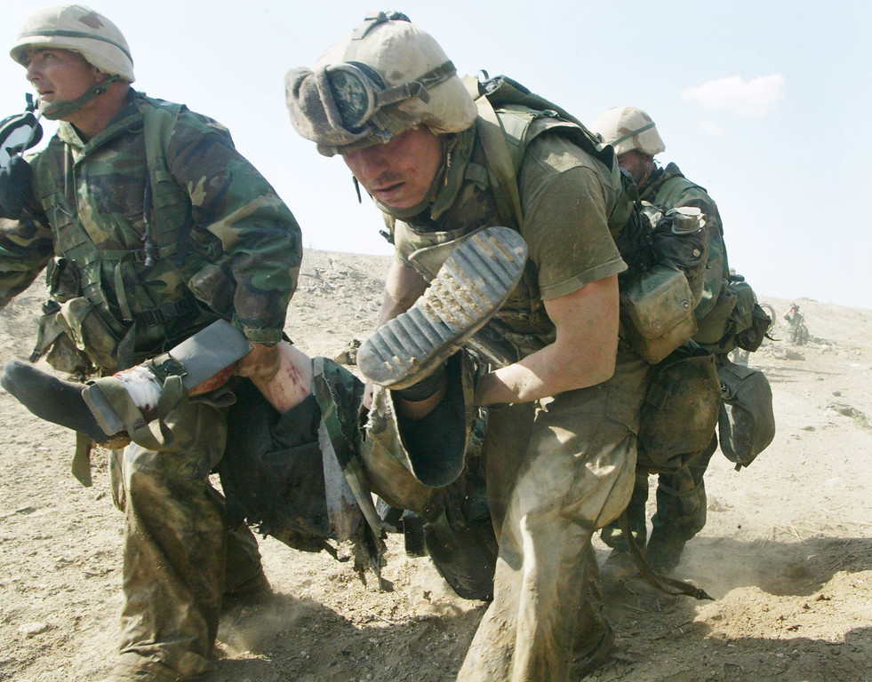 . U.S. Marines from Task Force Tarawa carry a wounded Marine during a gun battle March 23, 2003 in the southern Iraqi city of Nasiriyah. The Marines suffered a number of deaths and casualties during gun battles throughout the city. (Photo by Joe Raedle/Getty Images)