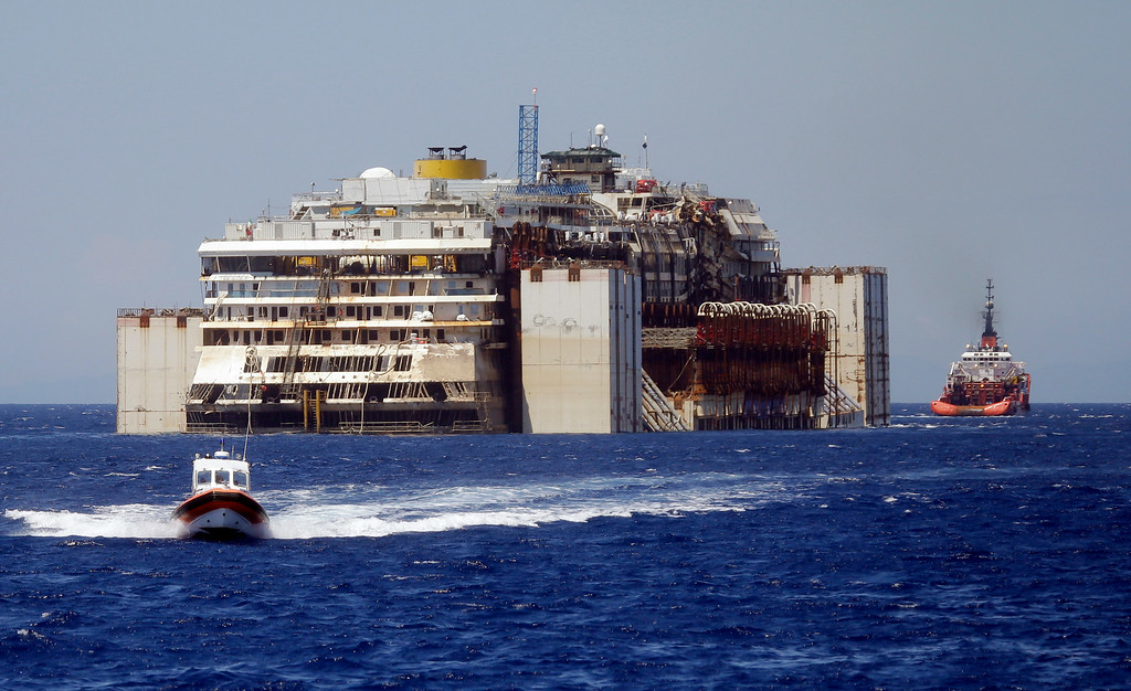 . The wreck of the Costa Concordia cruise ship is towed by two tugboats as it leaves behind the tiny Tuscan island of Isola del Giglio,  Italy, Wednesday, July 23, 2014. The Costa Concordia cruise liner has begun its final voyage away from the tiny Italian island where it capsized on Jan. 13, 2012, killing 32 people. (AP Photo/Gregorio Borgia)