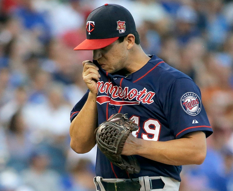 . Twins starting pitcher Tommy Milone wipes away sweat after giving up a run during the first inning against the Royals. Milone gave up four runs on nine hits in 5-1/3 innings. (AP Photo/Charlie Riedel)