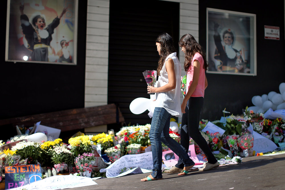 Description of . Relatives and friends of victims put flowers in front of the Kiss nightclub in Santa Maria, southern Brazil on January 29, 2013 where a blaze Sunday early morning left a death toll of over 230. Police in Brazil arrested four suspects Monday after a nightclub fire killed 231, left dozens more clinging to life, and forced officials to defend readiness for the Olympics and World Cup.  JEFFERSON BERNARDES/AFP/Getty Images
