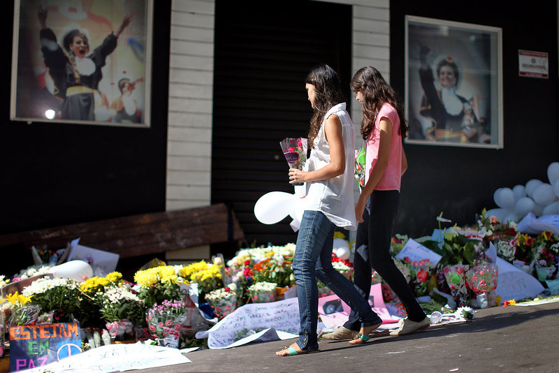 . Relatives and friends of victims put flowers in front of the Kiss nightclub in Santa Maria, southern Brazil on January 29, 2013 where a blaze Sunday early morning left a death toll of over 230. Police in Brazil arrested four suspects Monday after a nightclub fire killed 231, left dozens more clinging to life, and forced officials to defend readiness for the Olympics and World Cup.  JEFFERSON BERNARDES/AFP/Getty Images