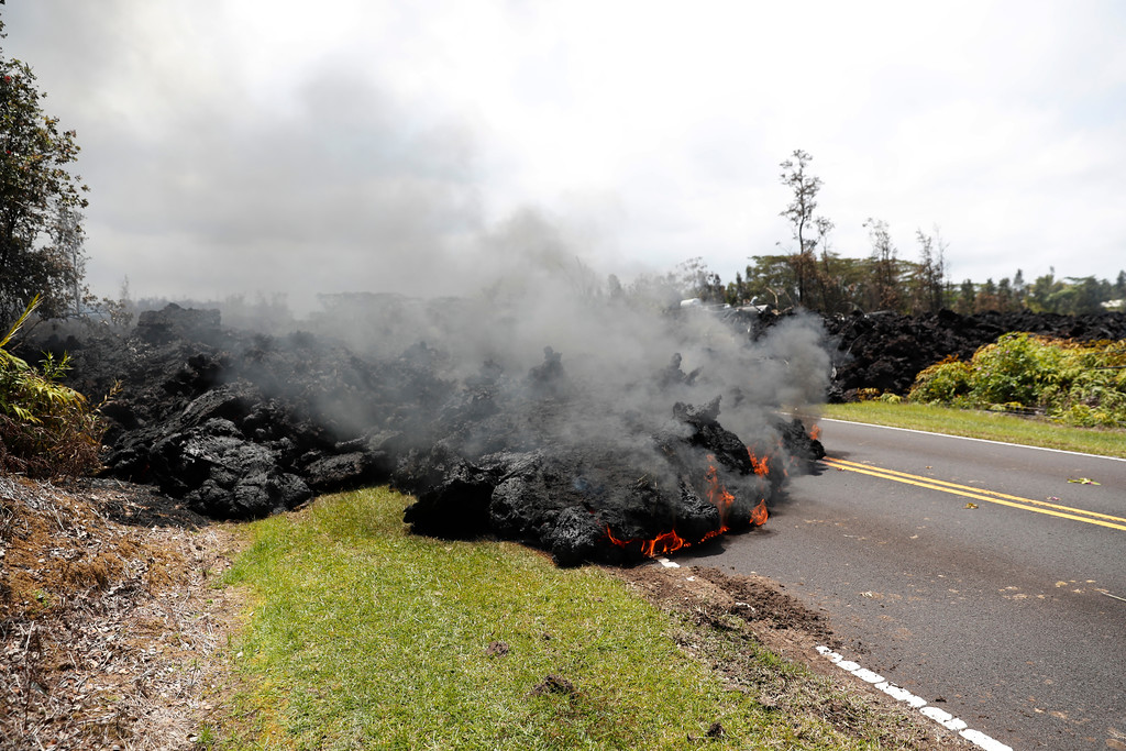 . Lava creeps across the road in the Leilani Estates subdivision, Saturday, May 5, 2018, in Pahoa, Hawaii. Hundreds of people on the Big Island of Hawaii are hunkering down for what could be weeks or months of upheaval as the dangers from an erupting Kilauea volcano grow. (AP Photo/Marco Garcia)