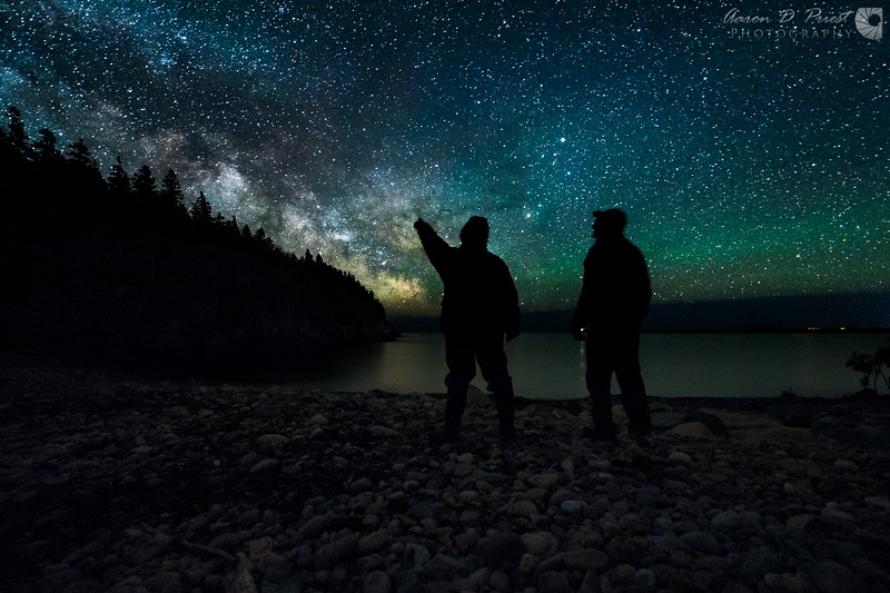 "Another successful night photography workshop with Acadia Images Photography Workshops has come to a close. What a great time we had! Here Mike Lawie and I enjoy the view from Hunter's Beach last night on May 20, 2015, 10:40 PM. I had scouted it out virtually some time ago with Photo Pills and Google Earth, and it predicted the Milky Way would rise along the edge of Hunter's Head, outlining its profile. Baker Island Lighthouse is visible in Mike's hand.<br /> <br /> We had some beautiful airglow, no saturation or vibrance has been added to this image. I masked two edits of the same RAW file in Photoshop to get some more shadow details of the ground. A special thank you to Mike's wife, Shelley, for pushing the shutter button for us! :-D<br /> <br /> Nikon D700 & 14-24mm f/2.8 @ 14mm, f/2.8, ISO 4000, 30 seconds, 3429°K<br /> <br /> Visit  <a href=""http://www.acadiaimages.com"">http://www.acadiaimages.com</a> for future workshops."