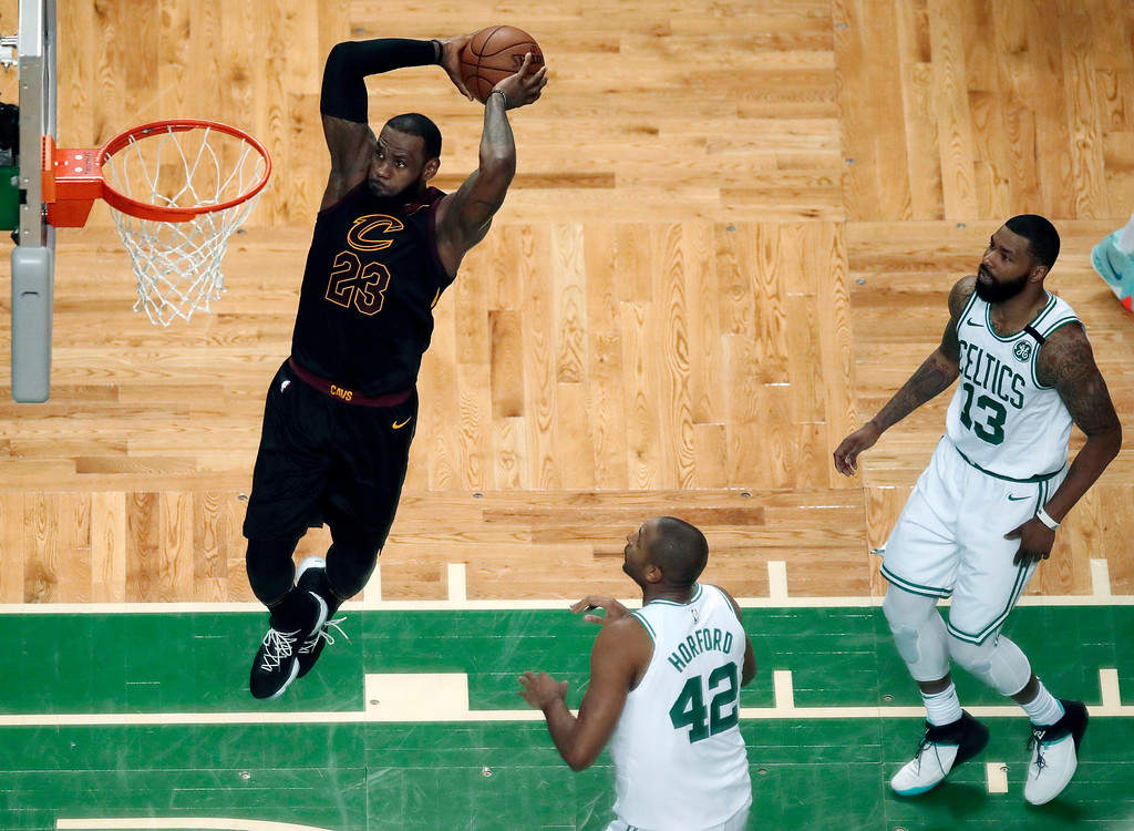 . Cleveland Cavaliers forward LeBron James soars to dunk in front of Boston Celtics forward Al Horford (42) and forward Marcus Morris (13) during the first half in Game 7 of the NBA basketball Eastern Conference finals, Sunday, May 27, 2018, in Boston. (AP Photo/Charles Krupa)