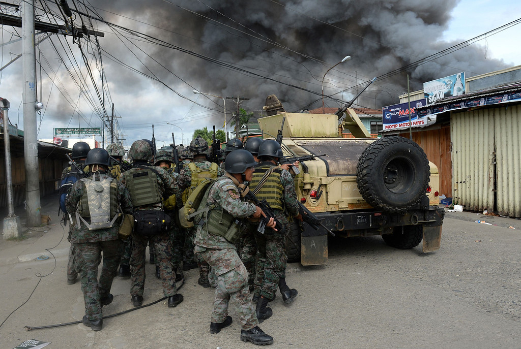 . Members of the Philippine national police special forces take cover as they move forward to enemy positions among burning houses during a fire fight with Muslim rebels, as a stand-off entered its fourth day in Zamboanga City on the southern island of Mindanao on September 12, 2013.   AFP PHOTO/TED ALJIBE/AFP/Getty Images