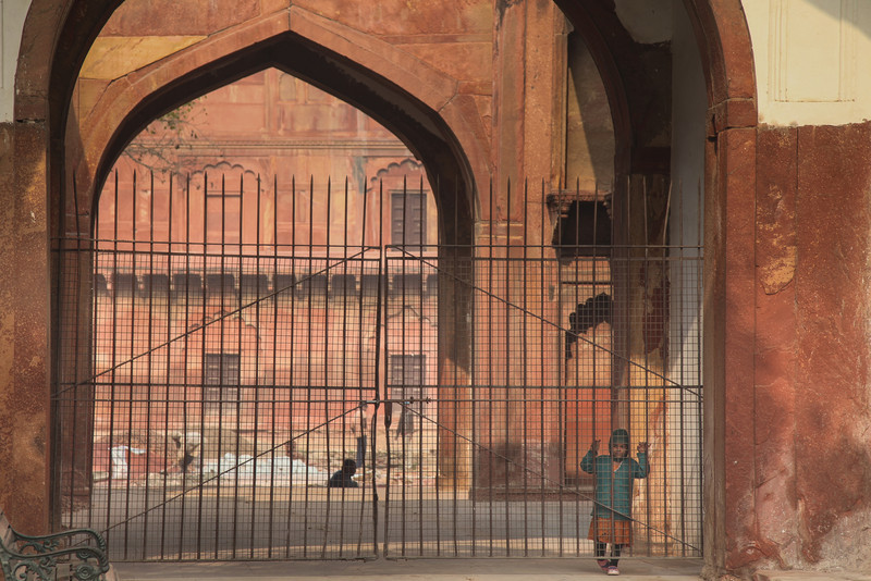 A child peers through a gate inside Agra Fort.