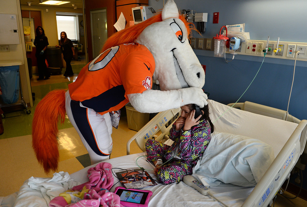 . Miles, the Broncos Mascot, gives a kiss on the head to patient  Karina Perez, 6, while she sits in her bed in the Pediatric Intensive Care Unit at the  Rocky Mountain Hospital for Children in Denver, Co on January 14, 2014. Perez is suffering from asthma.   (Photo By Helen H. Richardson/ The Denver Post)