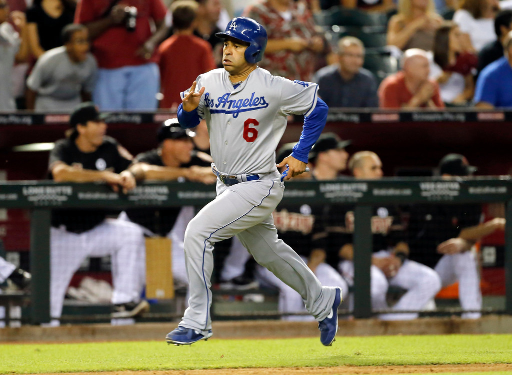 . Los Angeles Dodgers\' Jerry Hairston scores the tying run against the Arizona Diamondbacks during the ninth inning of a baseball game on a single by teammate Mark Ellis, Wednesday, July 10, 2013, in Phoenix. (AP Photo/Matt York)