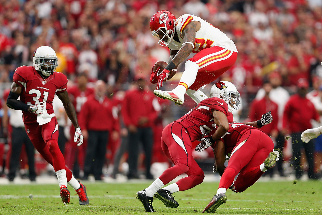 . GLENDALE, AZ - DECEMBER 07: Wide receiver Dwayne Bowe #82 of the Kansas City Chiefs leaps over free safety Rashad Johnson #26 of the Arizona Cardinals (right) and cornerback Justin Bethel #28 (left) during the second quarter of the NFL game at the University of Phoenix Stadium on December 7, 2014 in Glendale, Arizona.  (Photo by Christian Petersen/Getty Images)