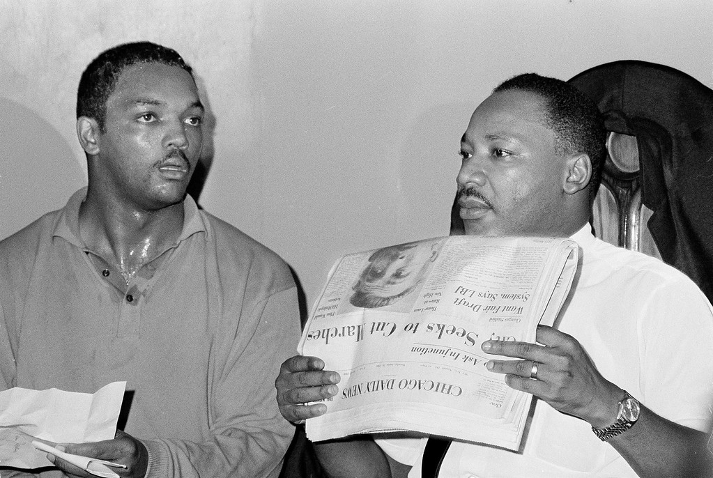 ". Civil rights leader Dr. Martin Luther King, Jr., right, and his aide Rev. Jesse Jackson are seen in Chicago, Aug. 19, 1966.  Dr. King holds a Chicago Daily News paper with a headline that reads ""City Seeks To Cut Marches.\""  During a meeting with 1,000 civil rights workers in a South Side church, King said, \""We aren\'t going to let any injunction turn us around.\""  (AP Photo/Larry Stoddard)"