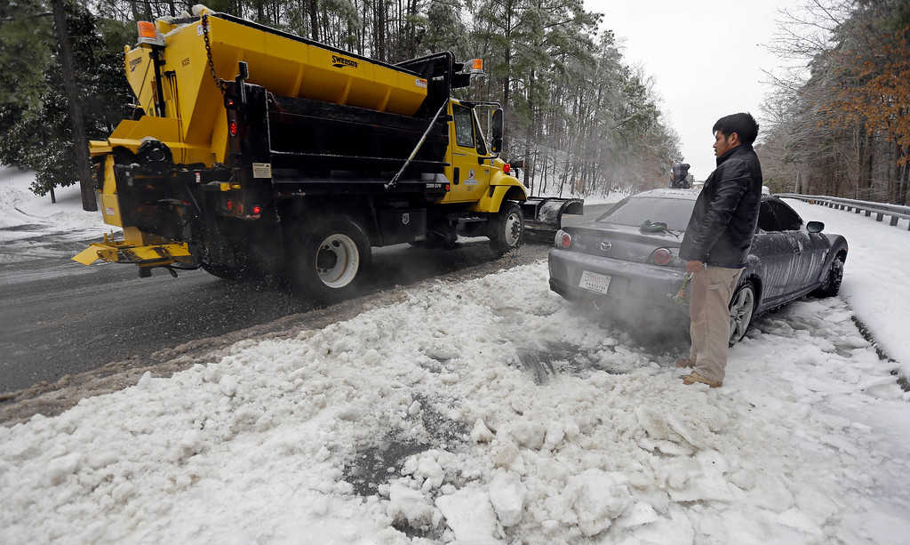 . Julian Ramirez watches a snow plow as he waits to dig his car from the frozen roadside after abandoning the vehicle overnight during the storm in Chapel Hill, N.C., Thursday, Feb. 13, 2014. The National Weather Service issued a winter storm warning lasting into Thursday covering 95 of the state\'s 100 counties. (AP Photo/Gerry Broome)