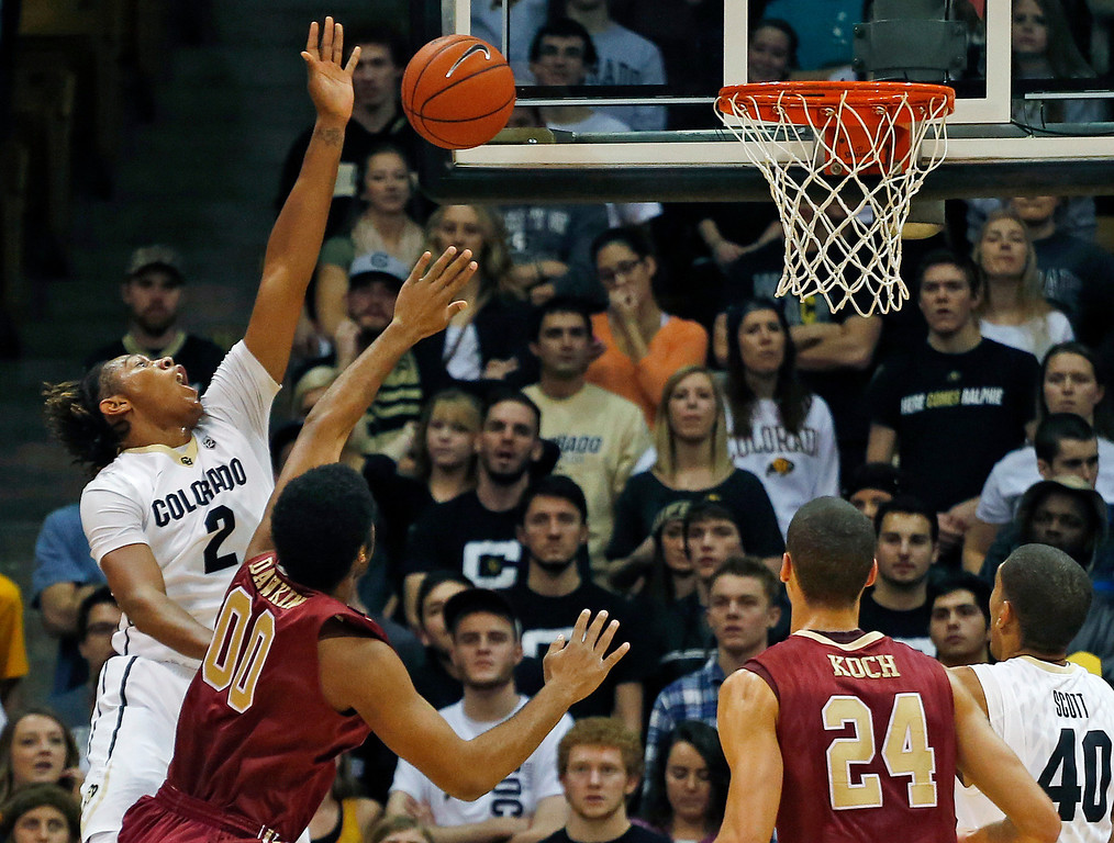 . Colorado\'s Xavier Johnson, left, is fouled by Elon\'s Brian Dawkins, second from left, during the first half of an NCAA college basketball game in Boulder, Colo., Friday, Dec. 13, 2013. (AP Photo/Brennan Linsley)