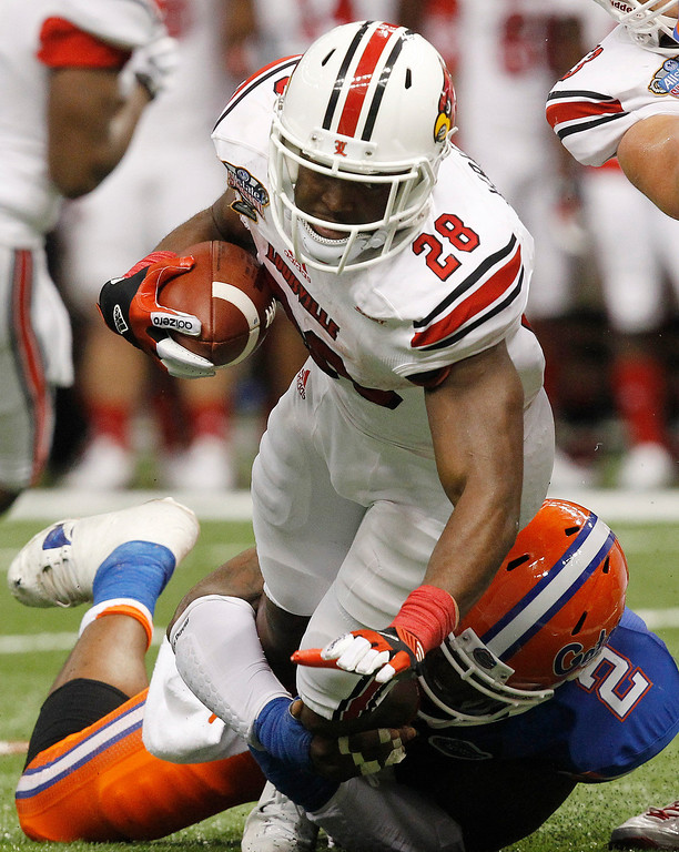 . Louisville running back Jeremy Wright (28) is stopped by Florida defensive lineman Dominique Easley (2) in the first half of the Sugar Bowl NCAA college football game Wednesday, Jan. 2, 2013, in New Orleans. (AP Photo/Butch Dill)