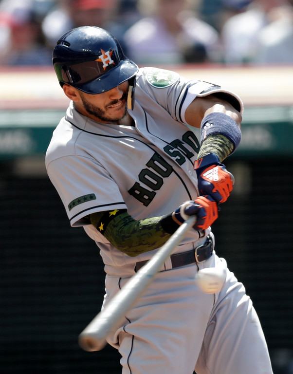 . Houston Astros\' Carlos Correa hits an RBI-single off Cleveland Cavaliers relief pitcher Evan Marshall in the eighth inning of a baseball game, Sunday, May 27, 2018, in Cleveland. Alex Bregman scored on the play. (AP Photo/Tony Dejak)