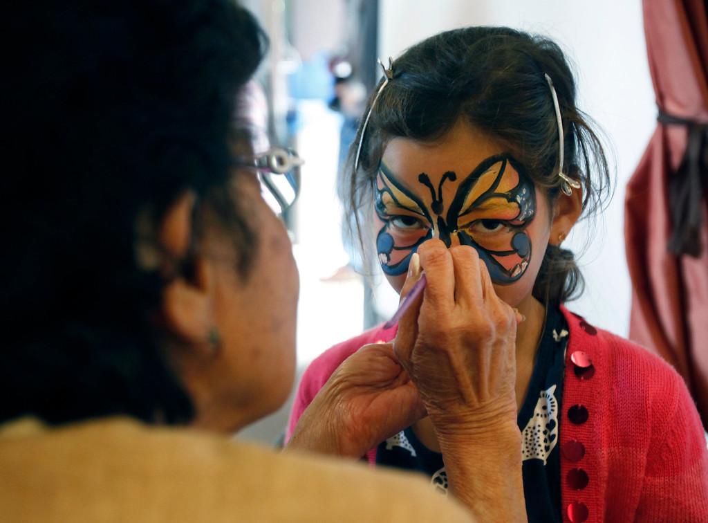 """. Seven-year-old Zoe Nguyen gets a butterfly face paint treatment from Rowena Chow at Hakone Estate and Gardens Lunar New Year of the Snake festival with a \""""Chinese Village Fair\"""" on Sunday afternoon, March 3, 2013 in Saratoga, Calif. (Karl Mondon/Staff)"""