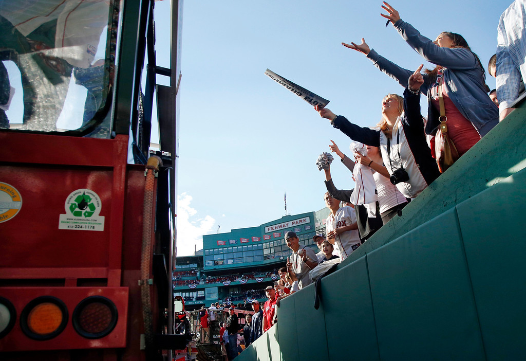 . Fans at Fenway Park reach out to a duck boat with Boston Red Sox players inside as they start a rolling rally to celebrate their World Series baseball championship in Boston, Saturday, Nov. 2, 2013. (AP Photo/Elise Amendola)