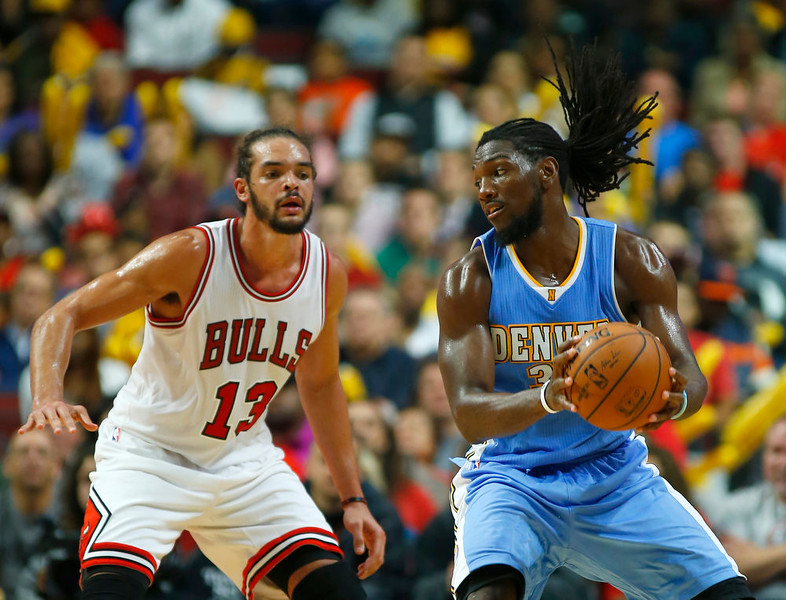 . Denver Nuggets forward Kenneth Faried (35) keeps the ball away from Chicago Bulls center Joakim Noah (13) during the second half of a pre-season NBA basketball game in Chicago, on Monday Oct. 13, 2014. The Bulls won the game 110-90. (AP Photo/Jeff Haynes)