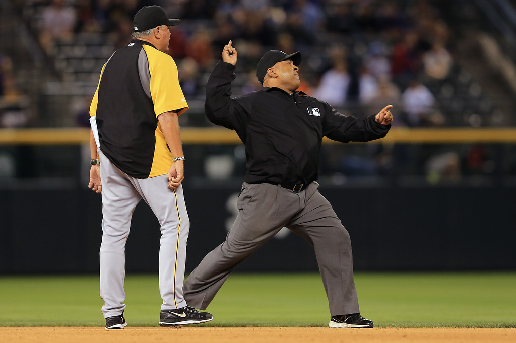 . DENVER, CO - AUGUST 10:  Manager Clint Hurdle #13 of the Pittsburgh Pirates is ejected from the game by second base umpire Adrian Johnson after arguing a call when Johnson called Alex Presley #7 of the Pittsburgh Pirates out in a double play by Troy Tulowitzki #2 of the Colorado Rockies in the seventh inning at Coors Field on August 10, 2013 in Denver, Colorado.  (Photo by Doug Pensinger/Getty Images)