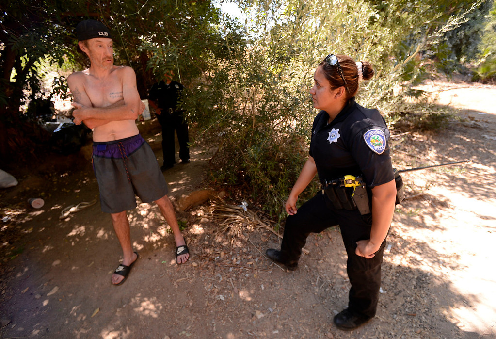 . San Bernardino Police Officer Sochilt Martinez, right,  questions Anthony Ethridge, 45, whose been living along the I-210 freeway in San Bernardino August 14, 2013. GABREL LUIS ACOSTA/STAFF PHOTOGRAPHER.