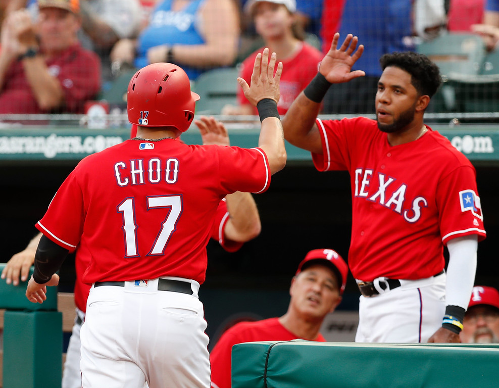 . Texas Rangers\' Shin-Soo Choo (17) celebrates his run scored with teammate Elvis Andrus on a single by Adrian Beltre against the Cleveland Indians during the first inning of a baseball game, Friday, July 20, 2018, in Arlington, Texas. (AP Photo/Jim Cowsert)