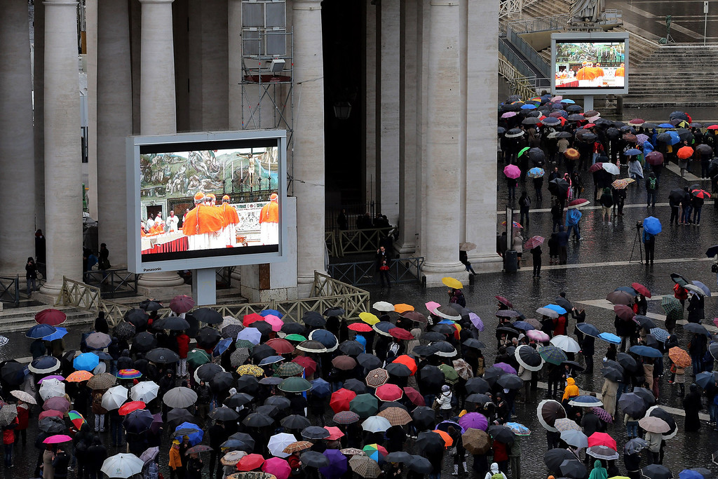 . People gather in St Peter\'s Square to watch large screens displaying live footage from inside the Sistine Chapel as Cardinals prepare for the first day of the conclave on March 12, 2013 in Vatican City, Vatican. (Photo by Joe Raedle/Getty Images)
