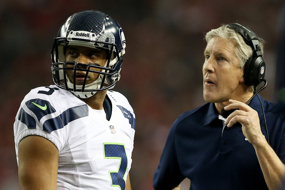. Russell Wilson #3 and head coach Pete Carroll of the Seattle Seahawks react during the second quarter against the Atlanta Falcons during the NFC Divisional Playoff Game at Georgia Dome on January 13, 2013 in Atlanta, Georgia.  (Photo by Streeter Lecka/Getty Images)