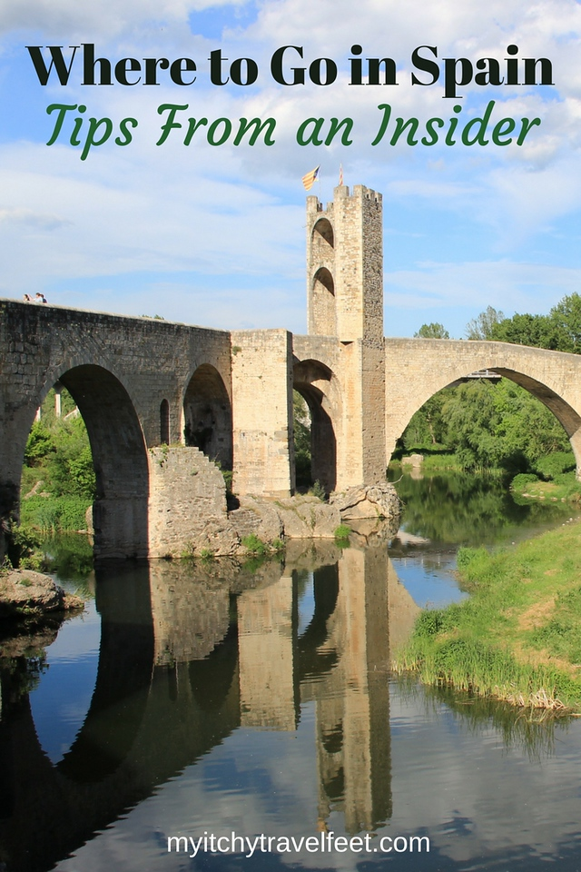 Text on photo: Where to Go in Spain, Tips From an Insider. Photo: Medieval bridge reflecting into the water in the Spanish countryside.