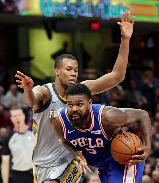 . Philadelphia 76ers\' Amir Johnson, right, drives past Cleveland Cavaliers\' Rodney Hood in the second half of an NBA basketball game, Thursday, March 1, 2018, in Cleveland. (AP Photo/Tony Dejak)