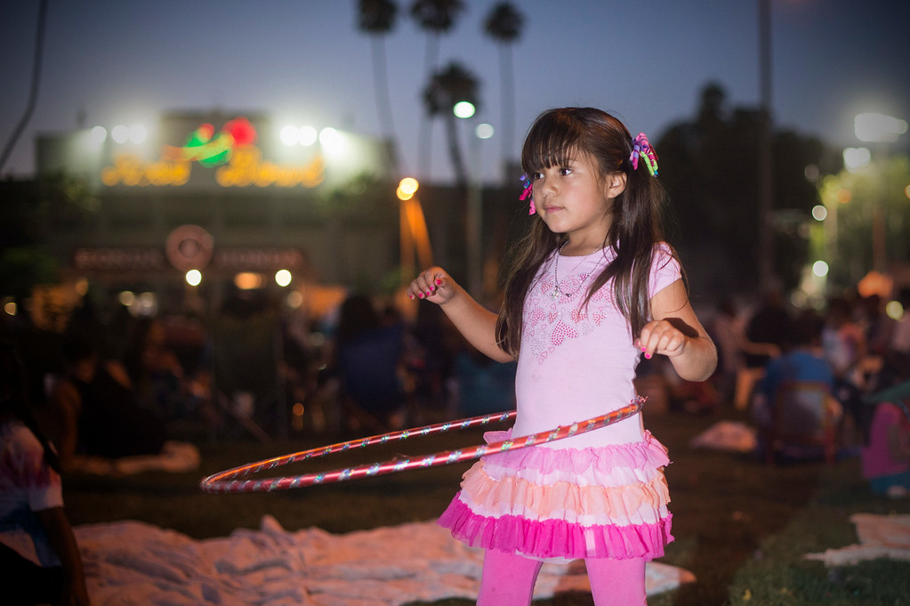 . Yesenia Aviles, 6, uses a Hula Hoop as the Martinez family and friends gather to watch Americafest\'s annual fireworks show at the Rose Bowl in Pasadena Friday night, July 4, 2014. The Martinez family has gathered every year to see the show to celebrate Sebastian Martinez\' birthdays since the 7-year-old was born on the Fourth of July. (Photo by Sarah Reingewirtz/Pasadena Star-News)