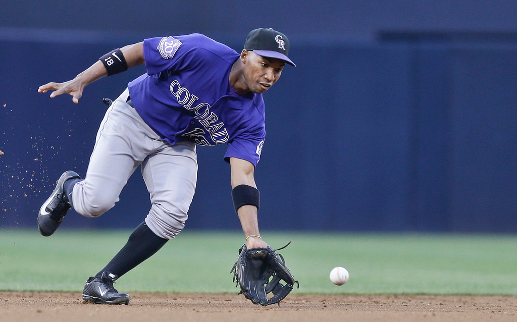 . Colorado Rockies shortstop Jonathan Herrera prepares to field  a slow bounce hit by San Diego Padres\' Everth Cabrera in the first inning of a baseball game in San Diego, Monday, July 8, 2013. Herrera got the out at first.  (AP Photo/Lenny Ignelzi)