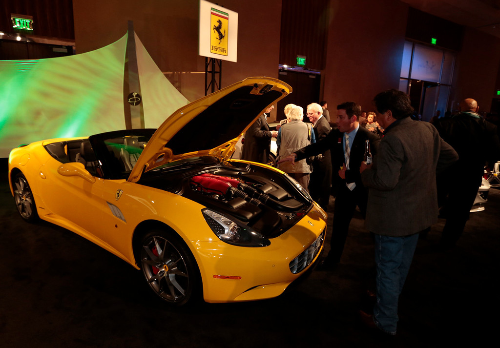 . Attendees view a yellow Ferrari SpA California at The Gallery in the MGM Grand Detroit ahead of the 2013 North American International Auto Show (NAIAS) in Detroit, Michigan, U.S., on Saturday, Jan. 12, 2013. The Detroit auto show runs through Jan. 27 and will display over 500 vehicles, representing the most innovative designs in the world. Photographer: Jeff Kowalsky/Bloomberg