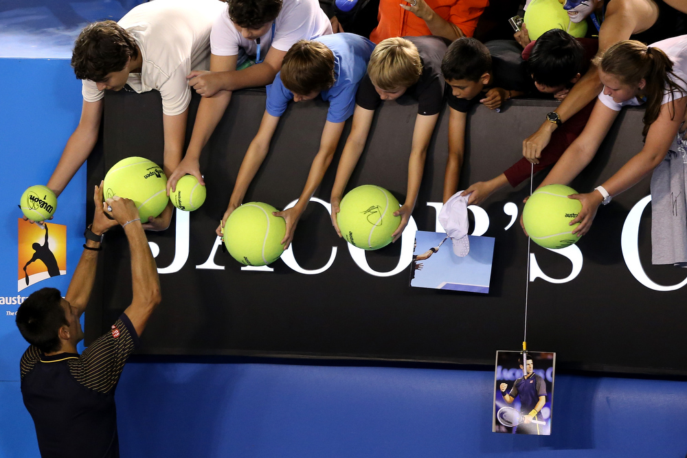 Description of . Novak Djokovic of Serbia signs autographs for fans after winning his Semifinal match against David Ferrer of Spain during day eleven of the 2013 Australian Open at Melbourne Park on January 24, 2013 in Melbourne, Australia.  (Photo by Michael Dodge/Getty Images)