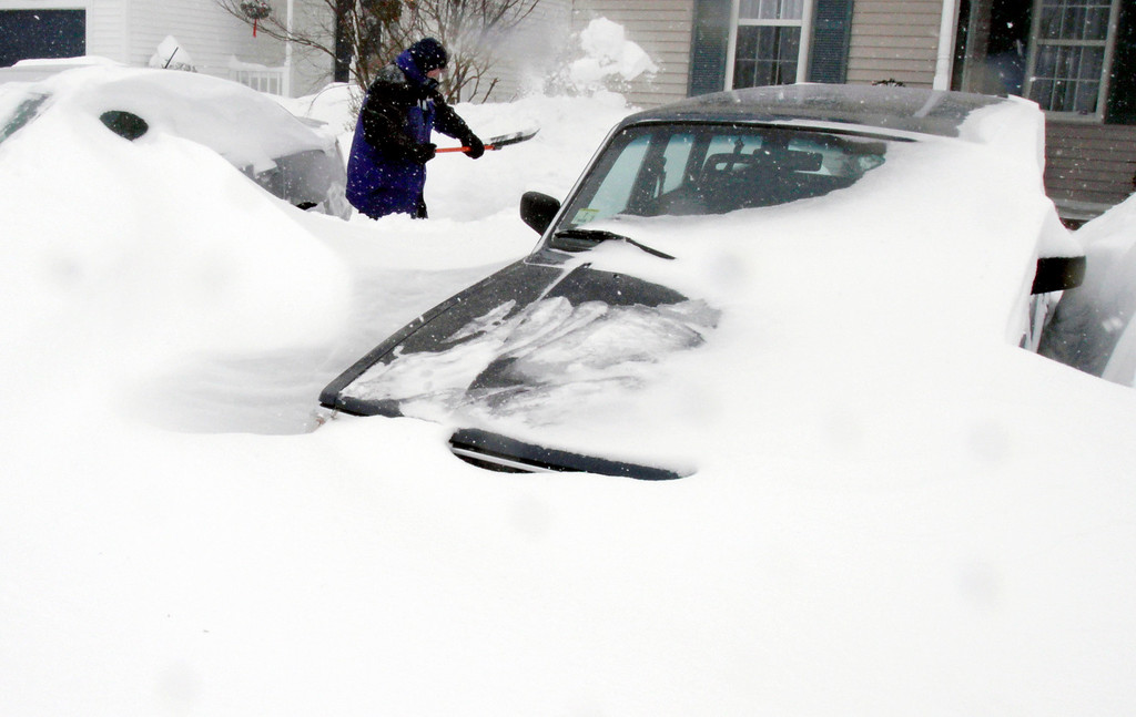 . Paul Baxter digs his cars out of drifted snow after a winter storm, Tuesday, Jan. 27, 2015, in Marlborough, Mass. A storm packing blizzard conditions spun up the East Coast early Tuesday, pounding parts of coastal New Jersey northward through Maine with high winds and heavy snow. (AP Photo/Bill Sikes)