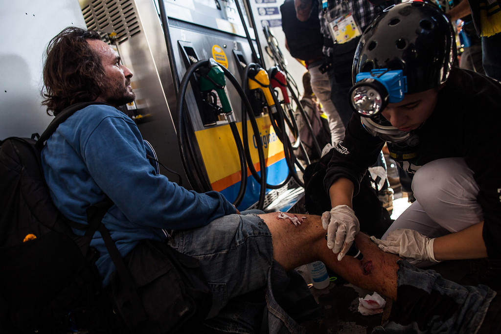 . AP Photographer Rodrigo Abd receives aid after being injured during the protest against the World Cup on the opening day of the event on June 12, 2014 in Sao Paulo, Brazil. Abd was allegedly shot by police who resonded to the protest. This is the first day of the 2014 FIFA World Cup. (Photo by Victor Moriyama/Getty Images)