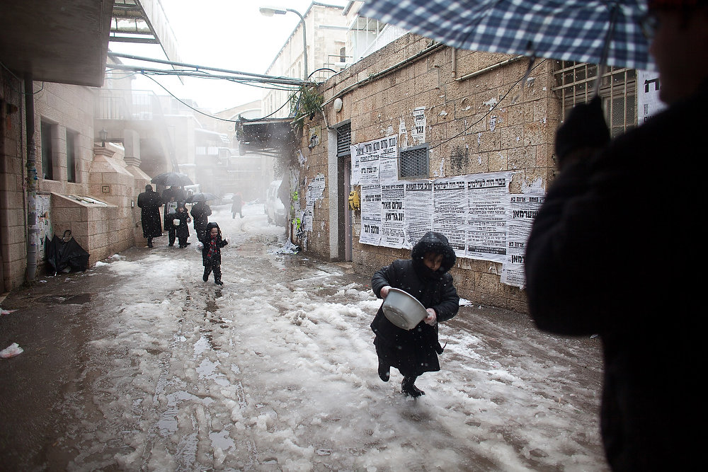 . Ultra-orthodox Jews enjoy the snow in the Mea Shearim religious neighborhood on January 10, 2013 in Jerusalem, Israel.  (Photo by Uriel Sinai/Getty Images)