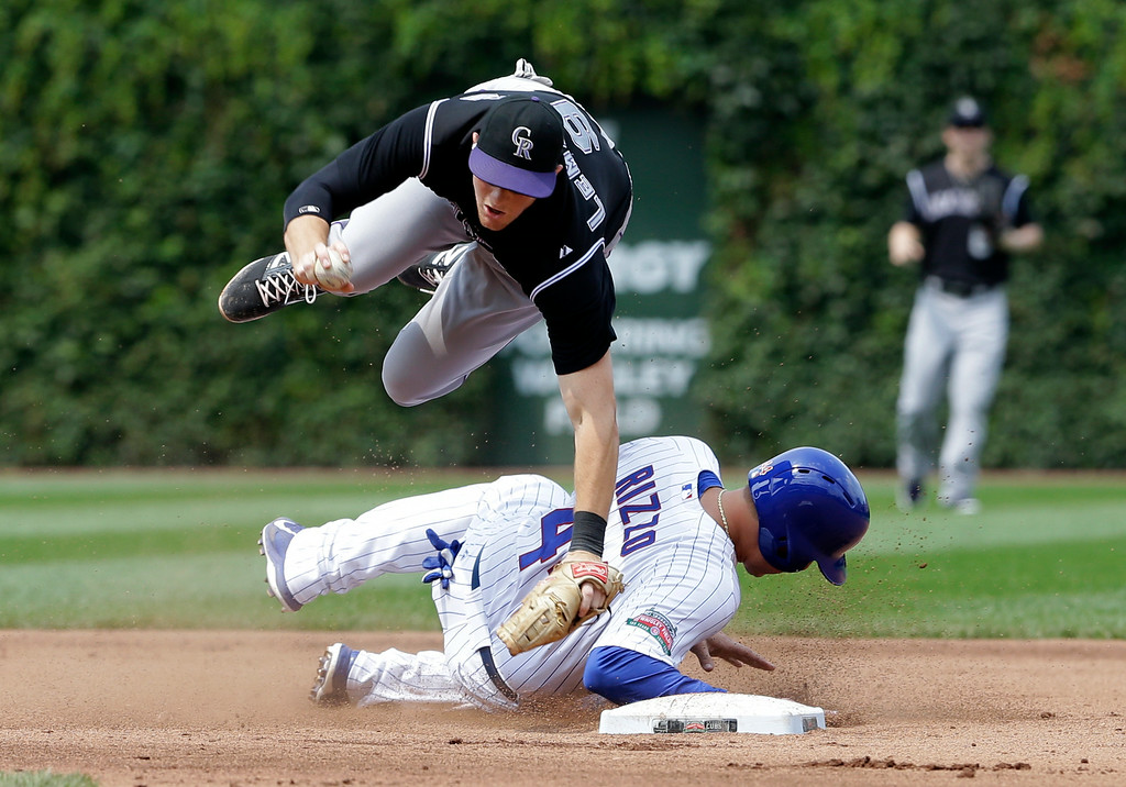 . Colorado Rockies second baseman D.J. LeMahieu, top,  jumps over Chicago Cubs\'  Anthony Rizzo after forcing him out at second base during the fourth inning of a baseball game in Chicago, Thursday, July 31, 2014. Starlin Castro was safe at first base on the play. (AP Photo/Nam Y. Huh)