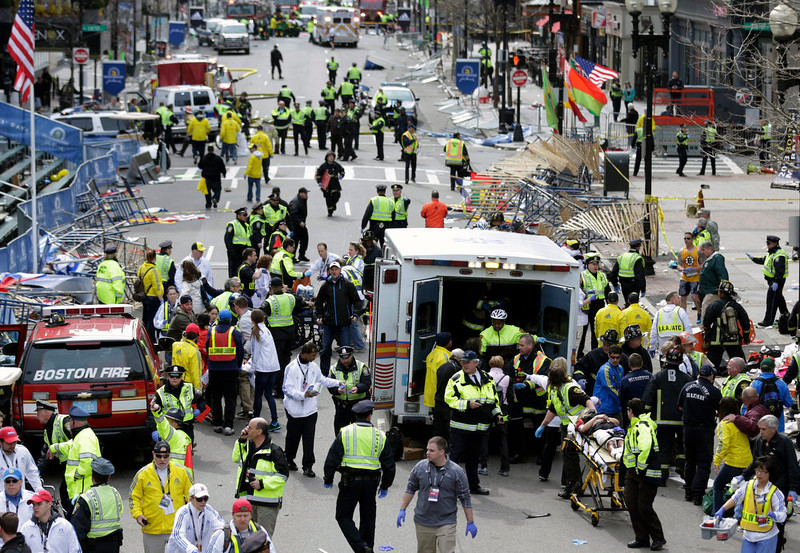 . Medical workers aid injured people at the finish line of the 2013 Boston Marathon following an explosion in Boston, Monday, April 15, 2013.  Two explosions shattered the euphoria of the Boston Marathon finish line on Monday, sending authorities out on the course to carry off the injured while the stragglers were rerouted away from the smoking site of the blasts. (AP Photo/Charles Krupa)