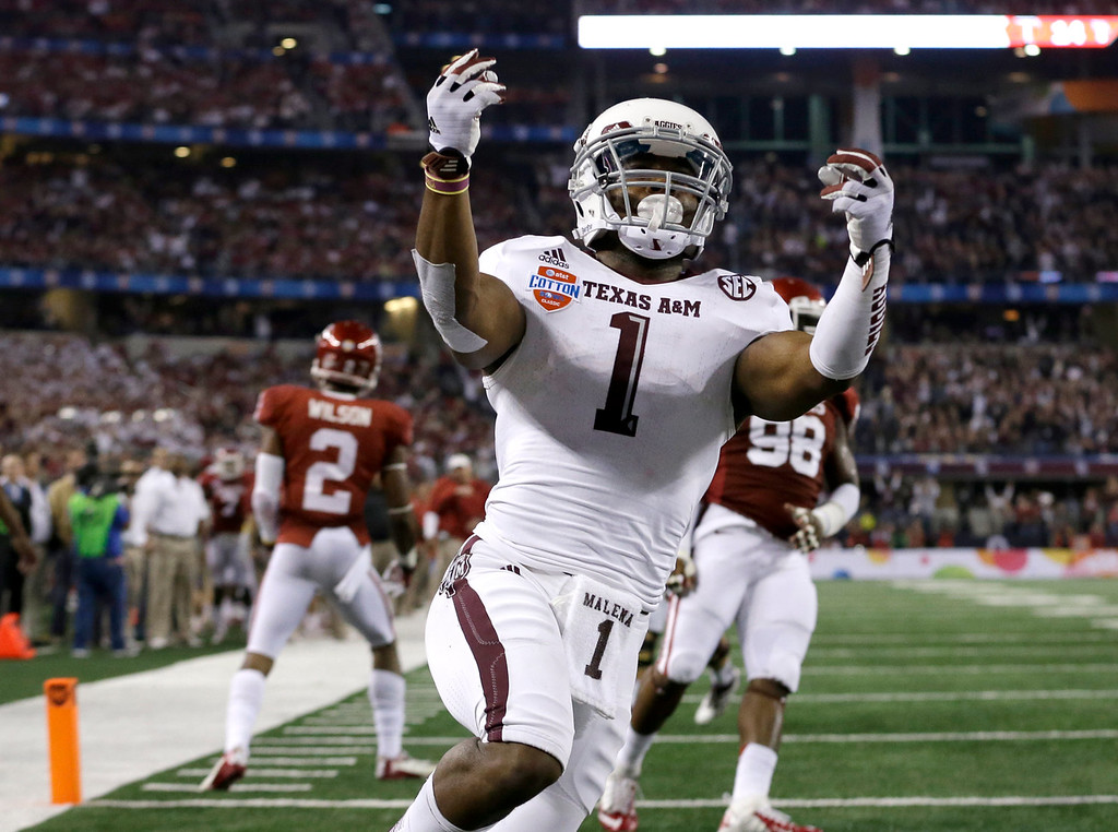. Texas A&M\'s Ben Malena (1) celebrates his touchdown as Oklahoma\'s Julian Wilson (2) and Chuka Ndulue (98) walk away in the second half of the Cotton Bowl NCAA college football game Friday, Jan. 4, 2013, in Arlington, Texas. (AP Photo/LM Otero)