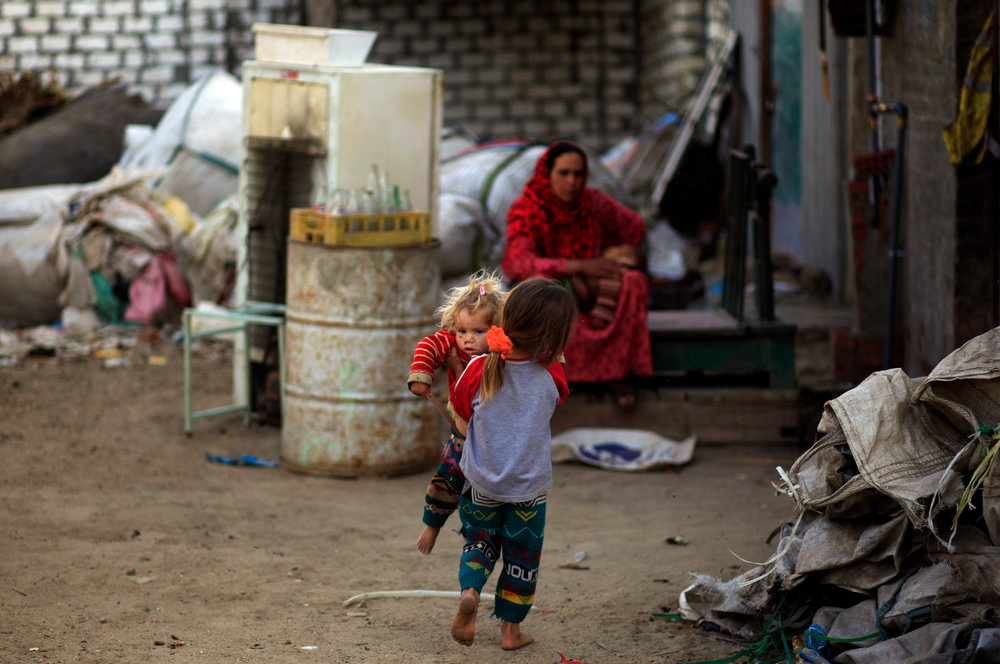 . A barefoot Palestinian refugee carries her sister outside their family\'s house in Gezirat al-Fadel village, Sharqiya, about 150 kilometers (93 miles) east of Cairo, Egypt.  (AP Photo/Khalil Hamra)