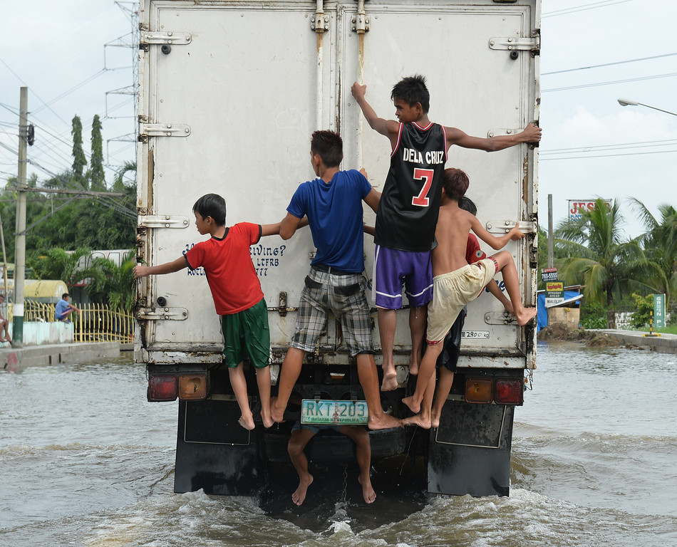 . Young boys affected by flooding due to heavy rains exarcebated by Tropical storm Trami ride on the back of a truck down a flooded street in the town of Calumpit, Bulacan province, north of Manila on August 22, 2013. Disaster-weary Philippine residents mopped up August 22 after four days of rains that officials said had killed 18 people and forced more than half a million from flooded homes. TED ALJIBE/AFP/Getty Images