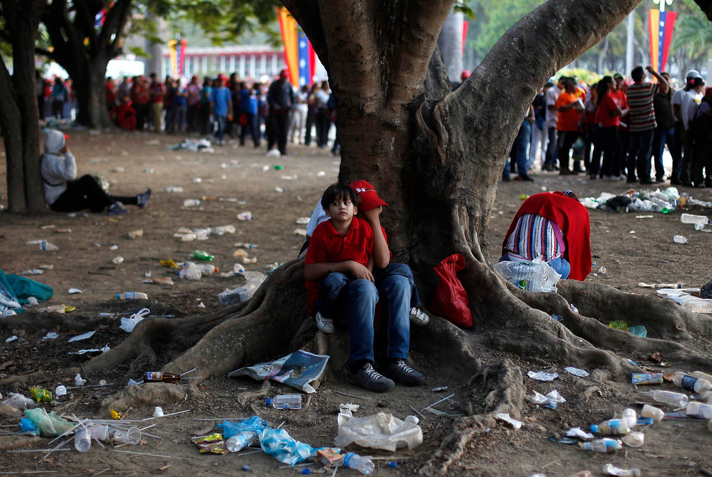 . Supporters of Venezuela\'s late President Hugo Chavez sit at a tree as they wait for a chance to view his body lying in state, at the military academy in Caracas March 8, 2013.         REUTERS/Tomas Bravo